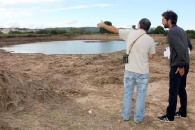 Ricardo Collado conversant amb un tècnic del Departament de Medi Ambient davant la llacuna permanent oberta a les Madrigueres. ACN