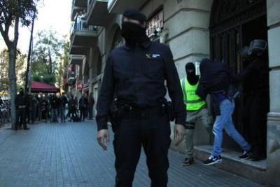 Uns agents de la Guàrdia Civil s'emporten detingut un dels homes acusats de captar persones per a Estat Islàmic. ACN