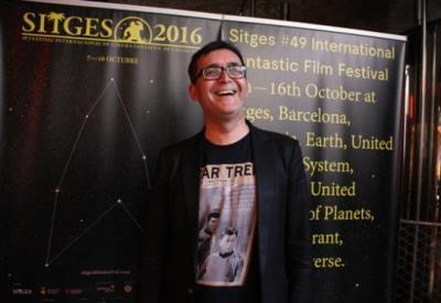 El director del Festival de Sitges, Ángel Sala, riu davant del cartell de la 49a edició del Festival (dedicat a l'univers 'Star Trek'), i llueix una s