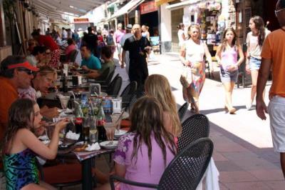 El carrer dos de maig de Sitges ple de turistes que passegen i mengen a la terrassa d'un restaurant. ACN