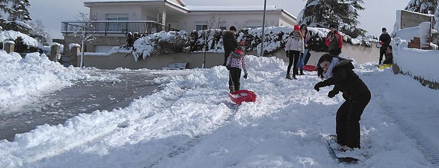 Pla general de diversos adolescents d'Ordal baixant per un carrer amb una taula d'snowboard mentre juguen amb la neu caiguda el 20 de març de 2018