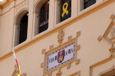 Detall del rètol de la Casa de la Vila de Sitges, amb un llaç groc a la part superior. Imatge del 21 de març del 2019. ACN