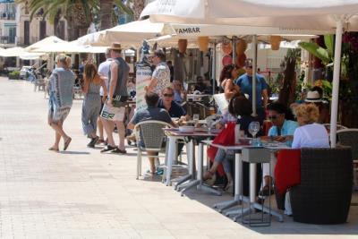 Pla general de la terrassa d'un restaurant de la platja de Sant Sebastià de Sitges plena de gent. ACN
