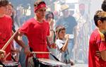 Pla mitjà lateral d'un dels menors estrangers no acompanyats acollits a Cubelles, tocant el timbal durant una cercavila de la Festa Major
