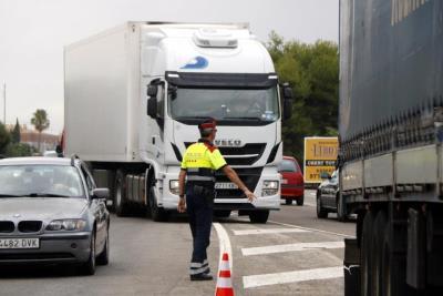 Pla obert d'un agent dels Mossos d'Esquadra aturant un camió a l'N-340, a l'alçada de Roda de Berà . ACN