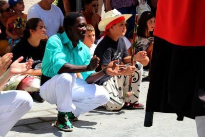 Pla obert d'un dels menors estrangers no acompanyats acollits a Cubelles, vestit amb camisa verda de geganter durant la Festa Major. ACN
