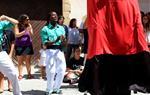 Pla obert d'un dels menors estrangers no acompanyats acollits a Cubelles, vestit amb camisa verda de geganter durant la Festa Major