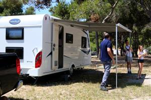 Pla general d'una família desplegant el tendal de la seva autocaravana en l'arribada a un càmping de Sitges, el 12 de juny del 2020