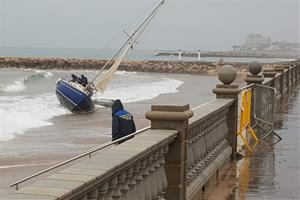 Troben una embarcació amb el motor encès encallada a una platja de Sitges